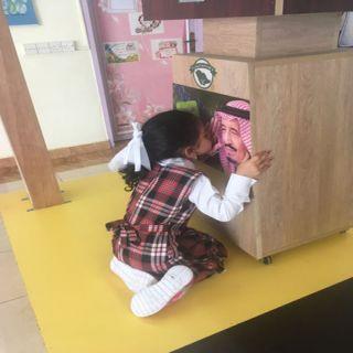 في روضة #محايل طفلة يتيمه تُقبل صورة الملك سلمان .. هذا والدي بعد أن مات والدي