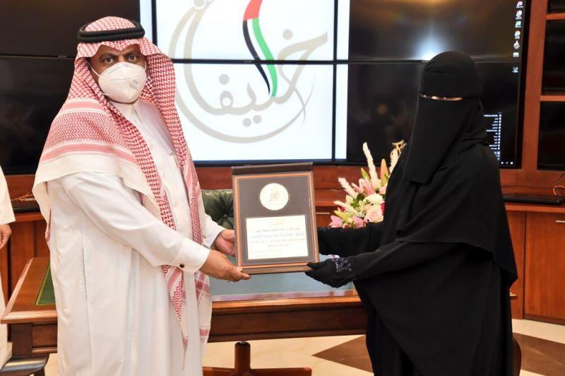 صورة لمُدير تعليم عسير سعد الجوني اثناء تسليم المُعلمة نادية جائزة خليفة التربوية للتعليم العام .